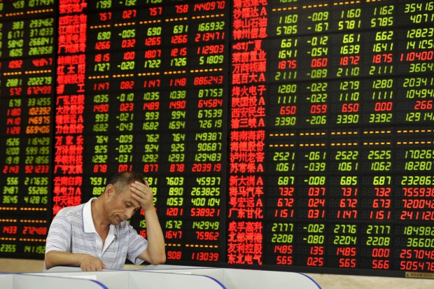 An investor looks at a computer screen in front of an electronic board showing stock information at a brokerage house in Fuyang, Anhui province, China, August 5, 2015. China stocks fell on Wednesday, regardles of both a promise by the central bank to stabilise market expectations and a private survey which showed activity in the services sector accelerated last month. REUTERS/Stringer CHINA OUT. NO COMMERCIAL OR EDITORIAL SALES IN CHINA - RTX1N4VD