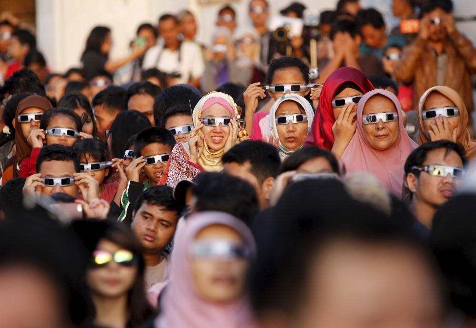 People watch a solar eclipse outside the planetarium in Jakarta, Indonesia March 9, 2016. REUTERS/Garry Lotulung