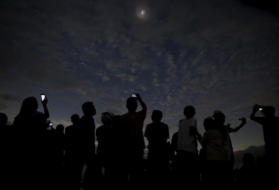 People watch and take pictures of the solar eclipse at the beach on Ternate island, Indonesia, March 9, 2016. REUTERS/Beawiharta