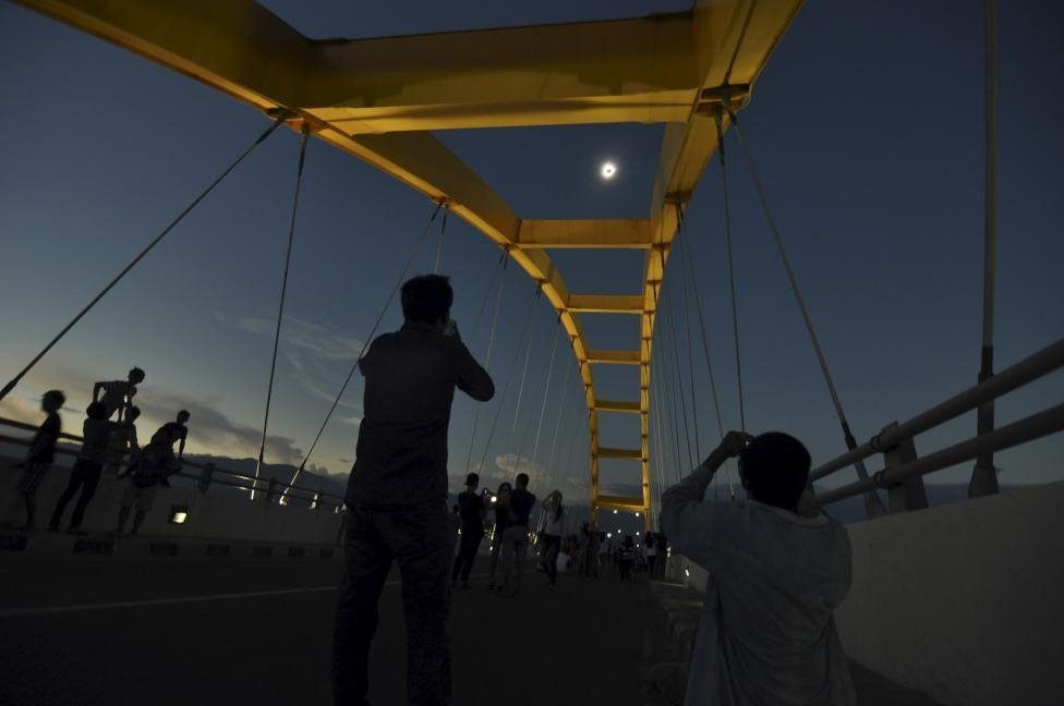 People watch a total solar eclipse from the Bay Bridge in Palu, Central Sulawesi, Indonesia March 9, 2016 in this photo taken by Antara Foto. REUTERS/Mohamad Hamzah/Antara Foto