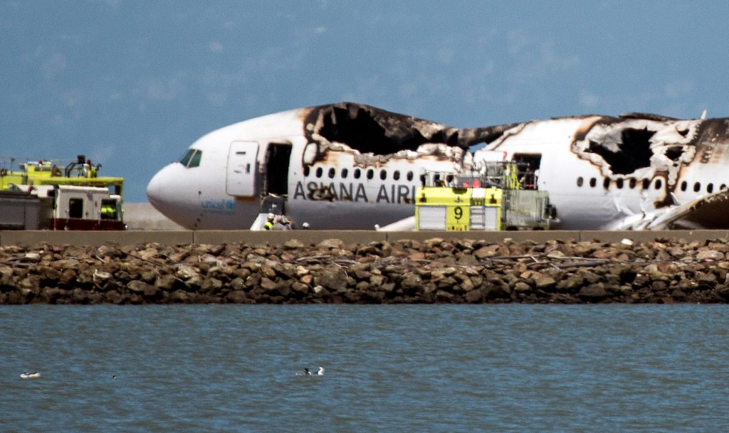 A burned Boeing Co. 777, operated by Asiana Airlines Inc., sits on the runway after it crashed landed at San Francisco International Airport (SFO) in San Francisco, California, U.S., on Saturday, July 6, 2013. The plane, on a flight from Seoul, South Korea, crashed while making a routine landing at San Francisco International Airport, killing two and burning as passengers escaped down emergency slides. Photographer: David Paul Morris/Bloomberg via Getty Images