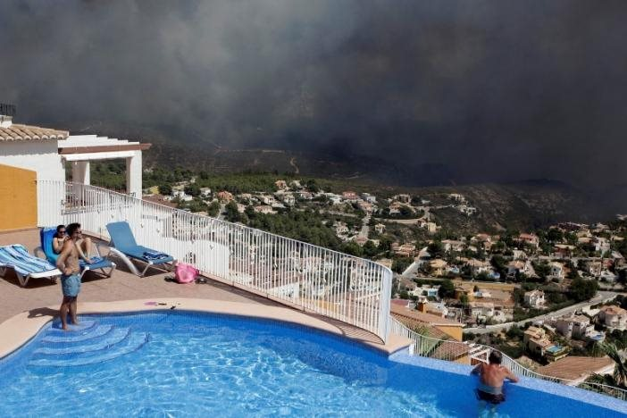 People at a pool observe a wildfire next to houses in Benitatxell near Alicante, Spain September 5, 2016. REUTERS/Heino Kalis