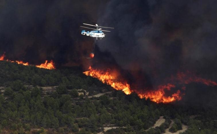 A firefighter helicopter flies over a wildfire engulfing a hillside in Benitatxell near Alicante, Spain September 5, 2016. REUTERS/Heino Kalis