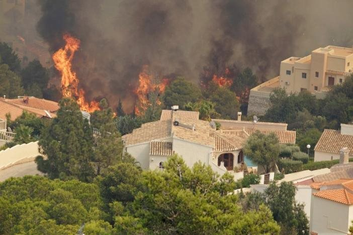 Trees burn next to houses during a wildfire in Benitatxell near Alicante, Spain September 5, 2016. REUTERS/Heino Kalis