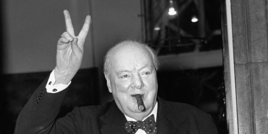 Sir Winston Churchill gives his familiar 'V' sign after a lunchtime meeting with American Secretary of State John Foster Dulles.