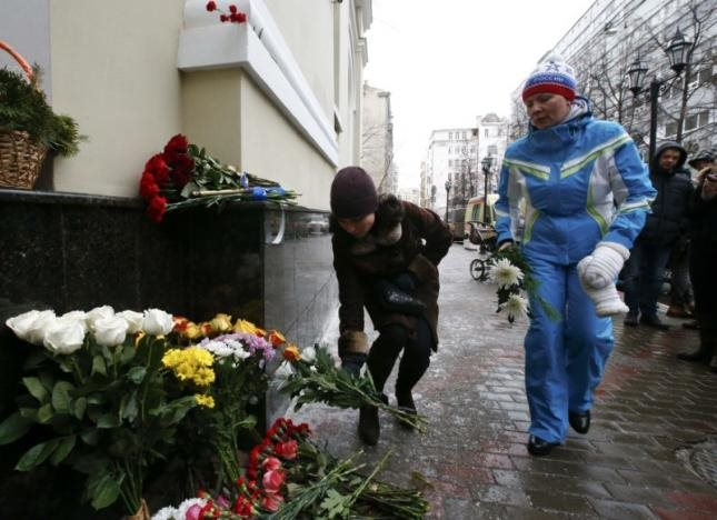 People lay flowers in memory of passengers and crew members of Russian military Tu-154 plane crashed into the Black Sea, outside the headquarters of Red Army Choir, also known as the Alexandrov Ensemble, in Moscow, Russia December 25, 2016. REUTERS/Sergei Karpukhin